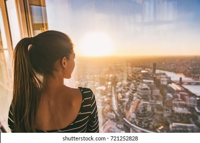 Europe travel woman looking at sunset view of London city skyline from the window of highrise skyscraper tower, famous tourist attraction in the U.K.