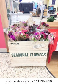 Europe UK Bedfordshire Bedford 11th June 2018. Inside major supermarket Tesco. Sign for seasonal flowers for sale in display box. Customers and computer tills in background at service counter.