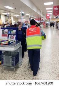 Europe UK Bedfordshire Bedford 12th April 2018. Inside major supermarket. Male and female staff members communicating at customer service checkout. Man wearing high visual jacket.
