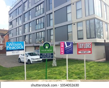 Europe UK Bedfordshire Bedford 25th March 2018. Estate agents advertising boards outside new block of flats. Urban setting with green grass landscape.
