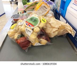 Europe UK Bedfordshire Bedford 30th April 2018. Inside major supermarket. Customer weekly food shopping on checkout conveyor belt. Close up bag of British grown potatoes.