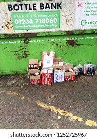 Europe UK Bedfordshire Bedford 8th December 2018. Outside in carpark. Major supermarket recycle bin for glass containers. Boxes of bottles left beside the container skip. Tesco bottle bank.