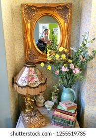 Europe UK Bedfordshire Bedford December 2018. Vintage style home decoration in sitting room. Older woman taking selfie in wall mirror.