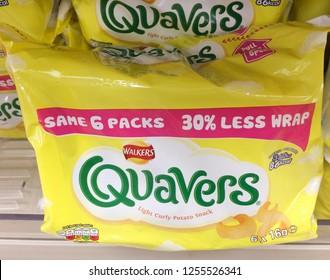 Europe UK Bedfordshire Bedford December 2018. Inside major supermarket food shelf. Yellow plastic bag of snacks. Green logo. Plastic wrapping text advertising.