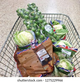 Europe UK Bedfordshire Bedford December 2018. Inside major supermarket. Food trolley with plastic wrapped vegetables.