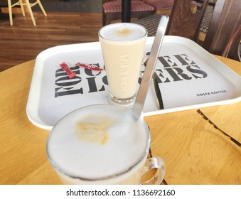 Europe UK Bedfordshire Bedford July 2018. Inside Costa Coffee shop. Two latte drinks on wooden round table. Pair of ladies brown glasses. White plastic tray with logo.
