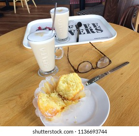 Europe UK Bedfordshire Bedford July 2018. Inside Costa Coffee shop. Two latte drinks on wooden round table. Pair of ladies brown glasses. Lemon muffin cake cut in half on white china plate.