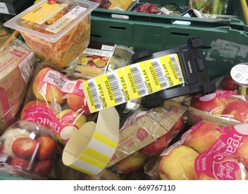 Europe UK Bedfordshire Bedford July 2017. Supermarket food in green crates ready to be reduced in price. Roll of reduced yellow stickers with bar codes in black plastic printing machine.