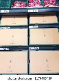 Europe UK Bedfordshire Bedford September 2018. Inside major supermarket. Vegetable section. Empty cardboard boxes upside down on shelves. Stock shelves with no selling products. Display racks.