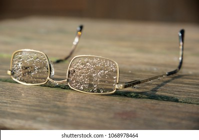 Europe UK Cambridgeshire Kimbolton 2003. Pair of spectacles covered in rain drops on wooden table. Closeup. Depth of field background.