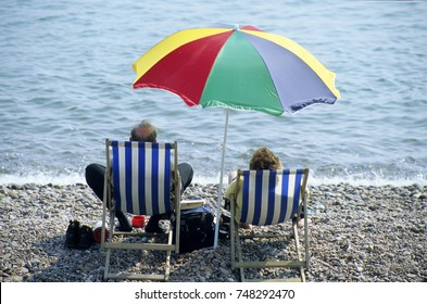 Europe UK Devon Sidmouth 1999. Seaside beach front. People sitting in deck chairs with  beach umbrella