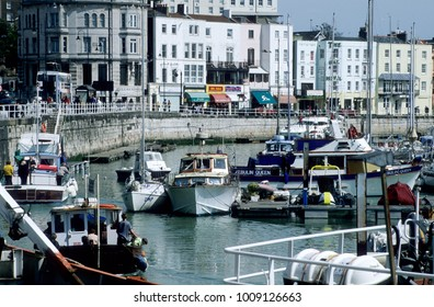 Europe UK District of Thanet East Kent Ramsgate 2000. Coastal town. Harbour wall and quayside. Moors boats inside harbour. Town houses on quayside.