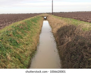 Europe UK East Lincolnshire Mablethorpe December 2017. Arable agricultural land. Winter. No crops. Ploughed fallow land with furrows. Water filled fen land drain.