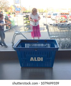 Europe UK Lincolnshire Louth 21st April 2018. Inside major supermarket. Supermarket logo on shopping basket on ledge by window. Blurred background with trolley park and customers.