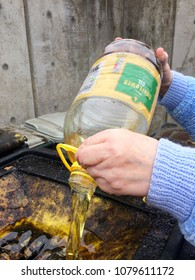 Europe UK Lincolnshire Louth 27th April 2018. Disposing of domestic cooking oil at the Recycling Plant. Woman pouring oil from plastic bottle into metal container.