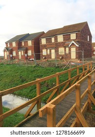 Europe UK Lincolnshire Sutton on Sea December 2018. New build houses with boarded windows. Unoccupied empty homes. Modern terrace vacant property housing development.