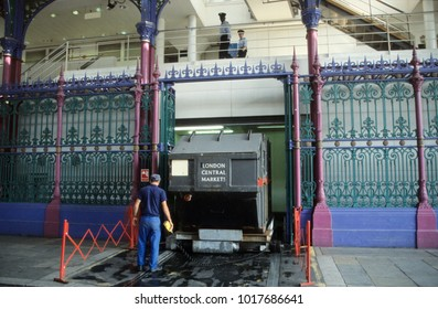 Europe UK London 2003. Smithfield Market. Man at work. Cleaning inside market after morning trading. Security police at work inside building watching photographer.