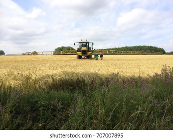 Europe UK North Bedfordshire July 2017. Farmers inspecting field of main crop ripe barley. Crop sprayer with booms extended in field of barley.