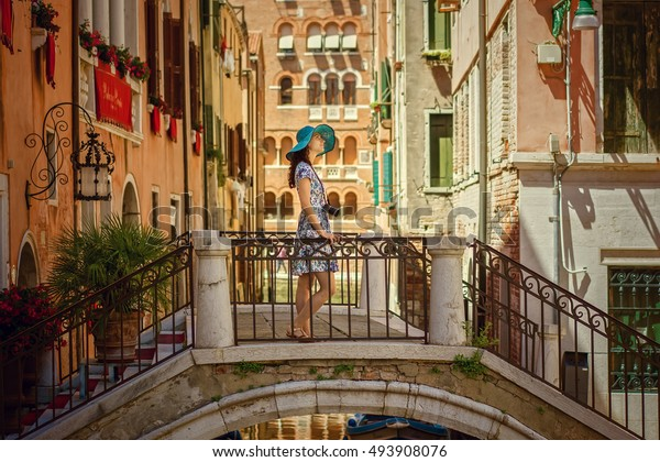 Europe urban travel vacation. Young woman in summer dress and blue hat style with camera posing on the bridge in Venice. Elegant lady traveling to Italy. Venice is popular place for traveling.