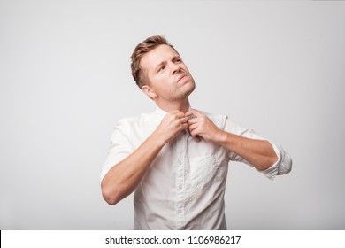 The europeam man in white shirt feeeling uncomfortable. Colar is tight and stuffy and he tries to expand the collar to make a breath. Hate office clothes