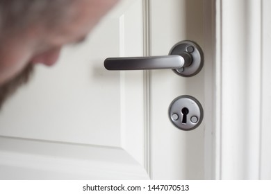 European 50 years old looks into the keyhole. Peeping man. Selective focus. Close-up