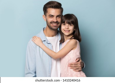 European appearance father and little daughter smiling looking at camera embracing posing isolated on blue studio background. Love, deep affection and devotion of preschool princess and daddy concept