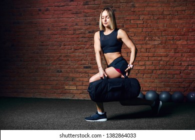 European athletic woman working out with sandbag while exercises in the gym over red brick wall background. Cross fit gym. Sport and Fitness concept.