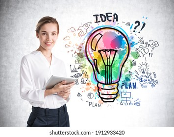 European attractive young woman in formal white shirt holding tablet device and pondering near concrete wall with colorful business idea lightbulb sketch drawn on it.