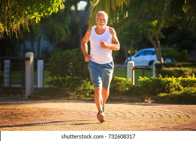 european bearded old man in white vest blue shorts does morning exercises runs along park against street