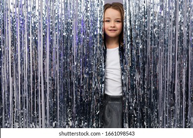 European beautiful teenage girl in a stylish outfit on a holiday peeks out from behind a tinsel background