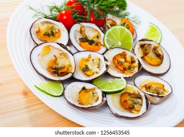 European bittersweet clam appetizers with lime, greens and vegetables