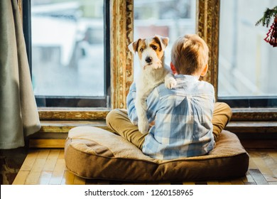 European blond boy and Jack Russel terrier sitting on the windowsill and look out the window at the snow. School age child and dog at home, winter day, cozy lifestyle concept.