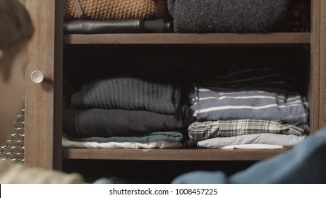 The European blond boy teenager brings wardrobe order, puts everything in its place, hides things in boxes. Wardrobe with women's, men's and child's clothing. Closet