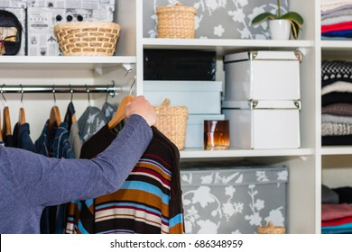 The European blond boy teenager brings wardrobe order, puts everything in its place, hides things in boxes. Wardrobe with women's, men's and child's clothing. Closet.