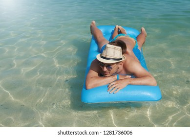 European boy and dad laying on blue floater on sea water surface.