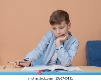 European boy sitting at the desk he is doing his home assignment. He is trying to solve difficult task.