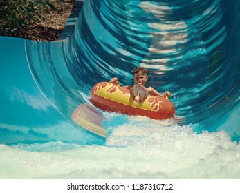 European boy slides down water slider on floater at waterpark.