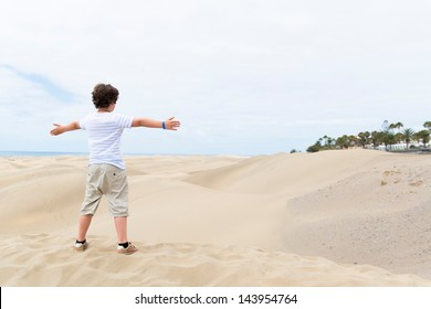 European boy stands on the sandy bottom of the outstretched hands