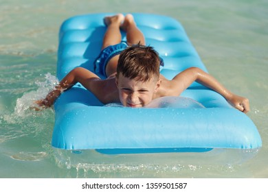 European boy in striped shorts is swimming on the blue floater. He is spending his vacations on Canarias.