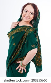 european brunette girl in green indian saree look at the camera and smiling on gray background in studio
