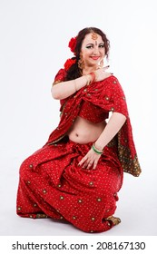 european brunette girl in red indian saree with her hands on her shoulder and hips on gray background in studio