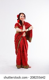 european brunette girl in red indian saree with her hands in namaste on gray background in studio