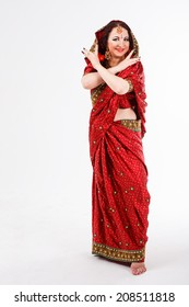 european brunette girl in red indian saree posing with her hands and smile at the camera in studio on gray background
