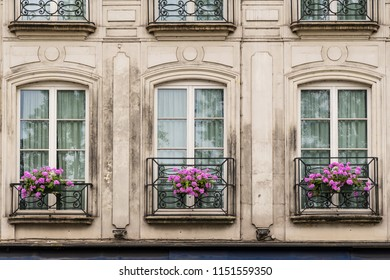 European building with flowers blooming in front of balcony windows.