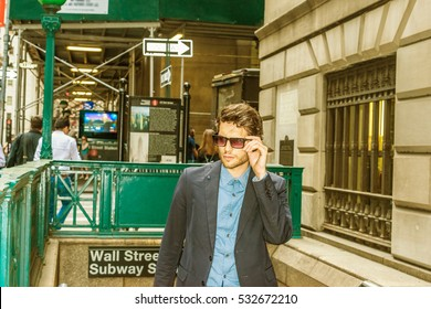 European Business Man traveling in New York. Dressing in blue suit, wearing sunglasses, young handsome man with beard confidently walking out from subway station, going to work. Color filtered effect.