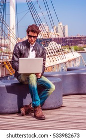 European Business Man traveling, working in New York, wearing black leather jacket, blue jeans, brown boot shoes, sunglasses, sits on bench at harbor, working on laptop computer. Color filtered effect