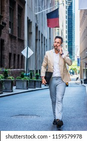 European Businessman traveling, working in New York City, with beard, little gray hair, wearing beige blazer, gray pants, leather shoes, holding briefcase, walking on street, talking on cell phone.