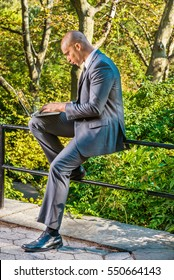 European Businessman travels, works in New York. Wearing gray suit, leather shoes, Mixed Race French man with shaved head sits on railing by woods, works on laptop computer. Color filtered effect.