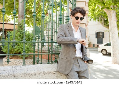 European businessman waiting in a classic city street and checking the time in his watch during a sunny day, outdoors.