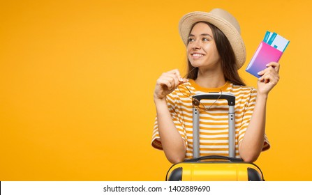 European Caucaian female dressed in summer clothes sitting at suitcase with airplane tickets dreaming about flight and trip, isolated